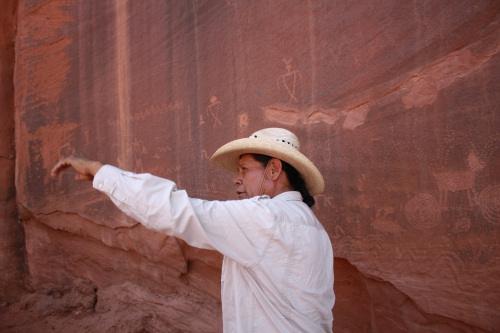 Clint Westwood of Monument Valley Safari in front of ancient petroglyphs