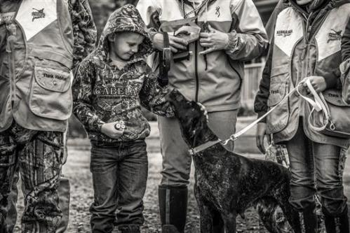 Kahne Packer and his German Shorthaired Pointer anxiously wait to set food afield at a youth mentor pheasant hunt at Cub Creek Hunting in Beatrice.  Photo by Kaleb White