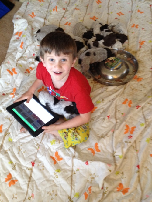 Caleb multi-tasking: holding a pup and playing on the iPad